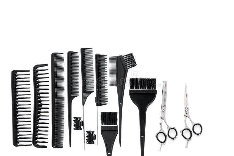 有工具的美发师运转的书桌为称呼在白色书桌背景顶视图嘲笑的头发  库存照片