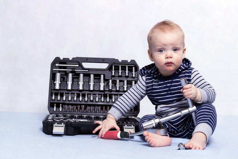 有工具箱和可调扳手的小孩男孩在他的手上 水平的演播室射击 图库摄影