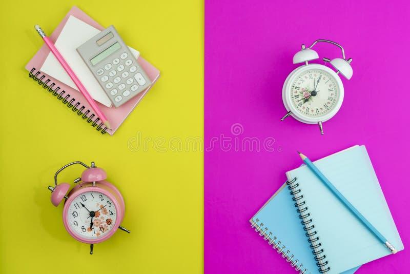 有工商业票据笔记、计算器和铅笔的新的闹钟在五颜六色的纸的颜色背景 图库摄影