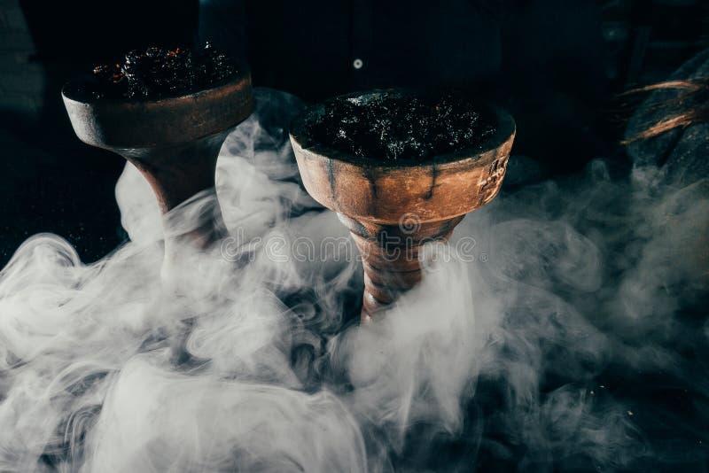 有工艺烟草和红色煤炭的Shisha碗有水烟筒蓝色和红色烟背景 免版税库存图片