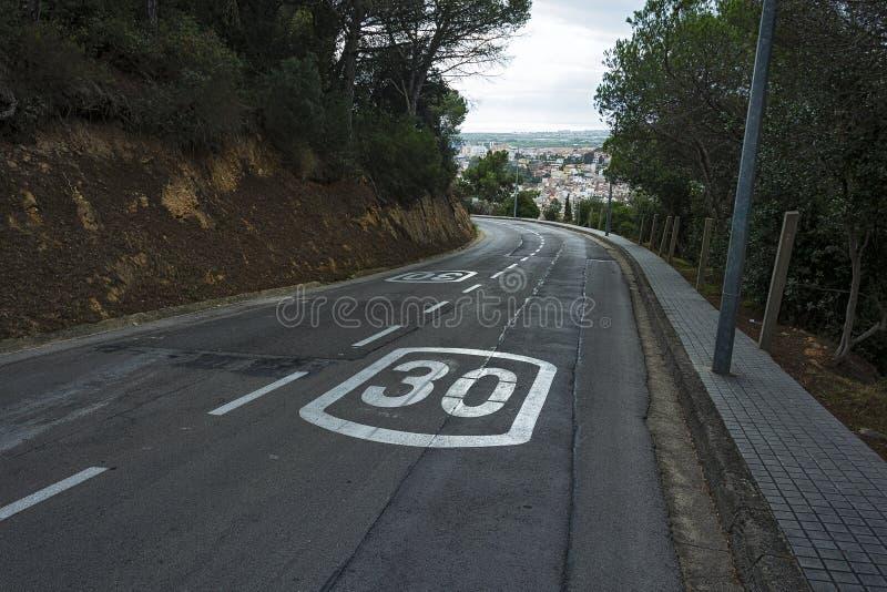 有左拐和限速的窄路 免版税库存照片