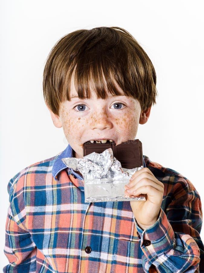 有巧克力块的愉快的红发男孩 库存图片