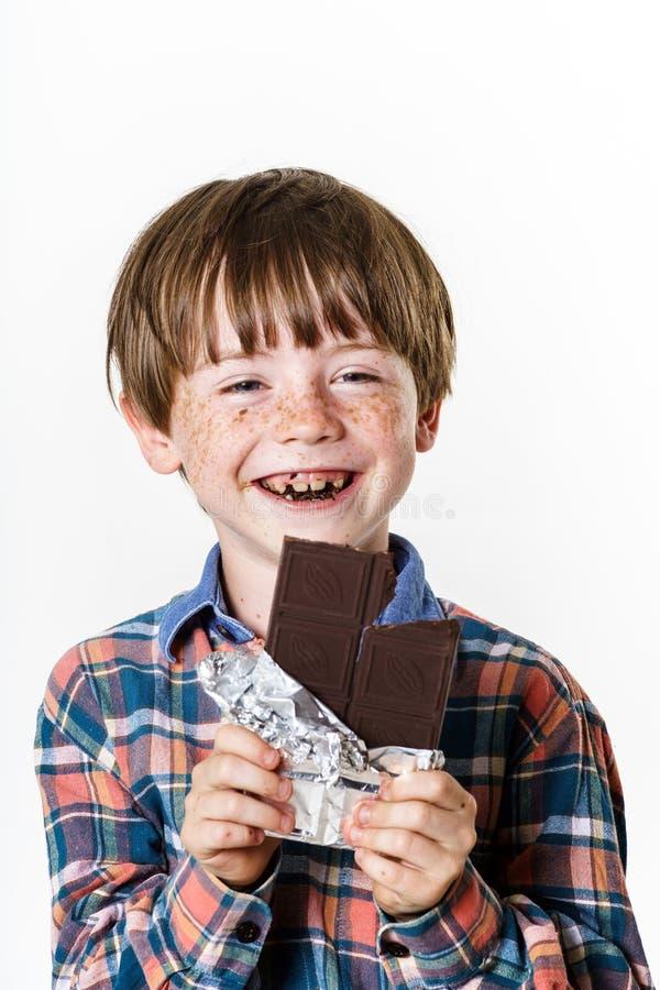 有巧克力块的愉快的红发男孩 图库摄影