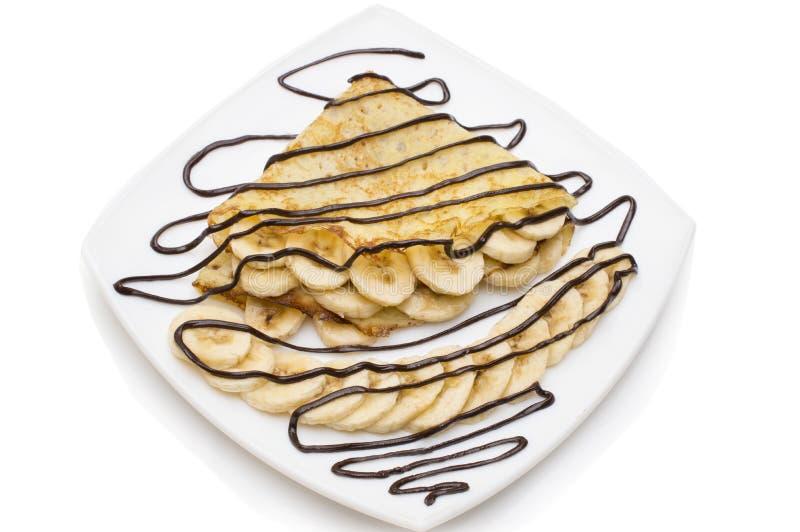 有巧克力奶油和香蕉的绉纱在白色背景 免版税图库摄影