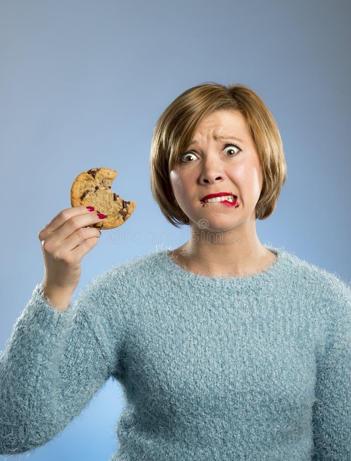 有巧克力污点的逗人喜爱的美丽的妇女在嘴吃大可口曲奇饼的 免版税库存照片