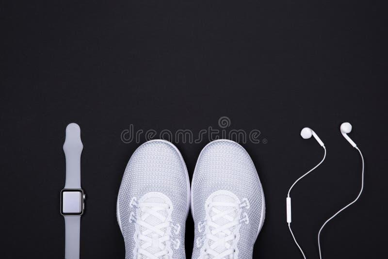 有巧妙的手表活动跟踪仪和耳机耳机的白色运动鞋运动鞋在黑色背景 免版税库存照片