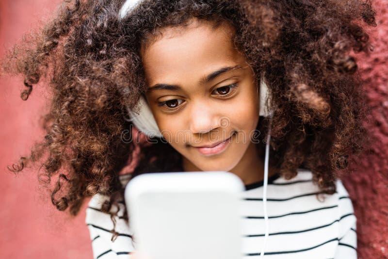 有巧妙的电话和耳机的美丽的非裔美国人的女孩 免版税库存照片