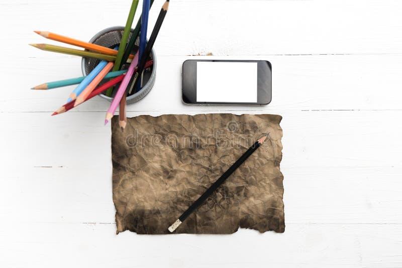 有巧妙的电话和铅笔的灼烧的棕色paer 图库摄影