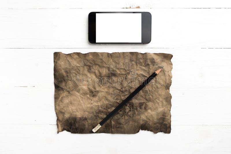 有巧妙的电话和铅笔的灼烧的棕色paer 免版税库存图片