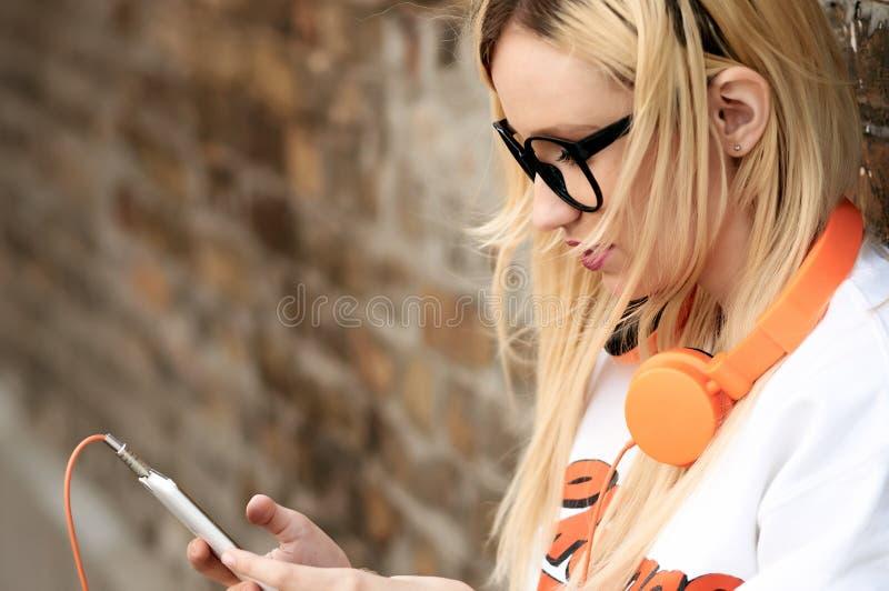 有巧妙的电话的年轻可爱的金发碧眼的女人听到音乐的室外 图库摄影