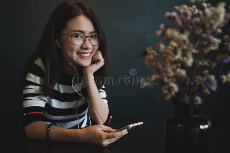 有巧妙的电话的年轻美丽的妇女,使用有耳机的快乐的少妇智能手机在黑背景 图库摄影