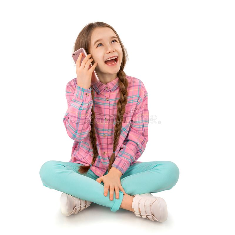 有巧妙的电话的愉快的小女孩坐在白色背景隔绝的地板 人们,孩子,技术 免版税库存照片