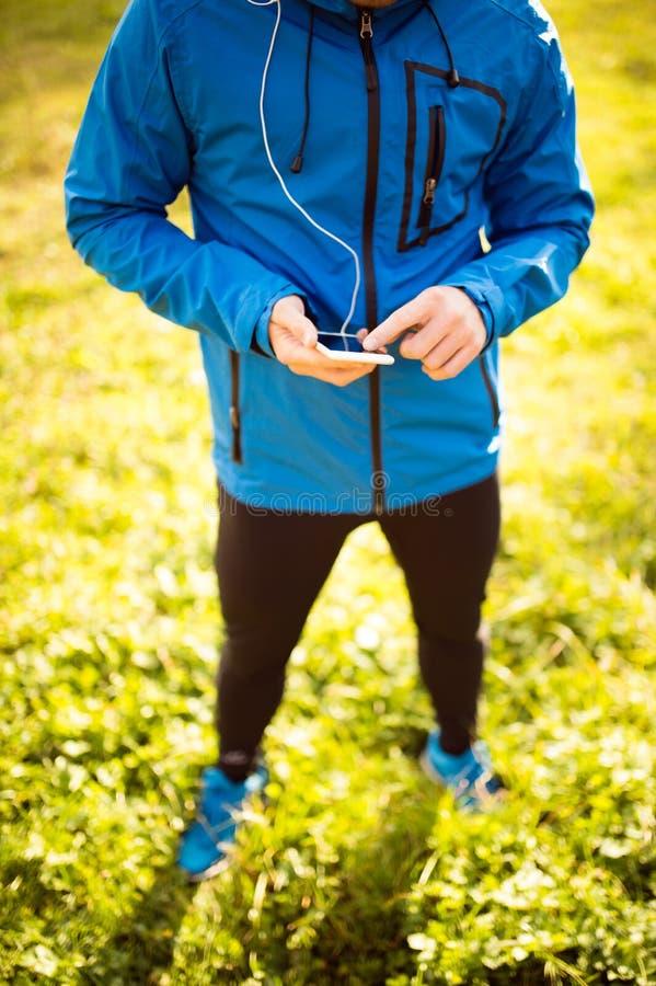 有巧妙的电话的无法认出的赛跑者,使用健身app 免版税图库摄影