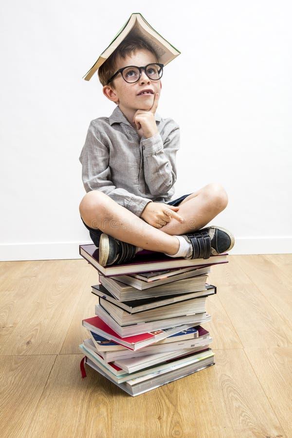 有巧妙的镜片的半信半疑的男小学生有在他的头的书的 免版税库存图片