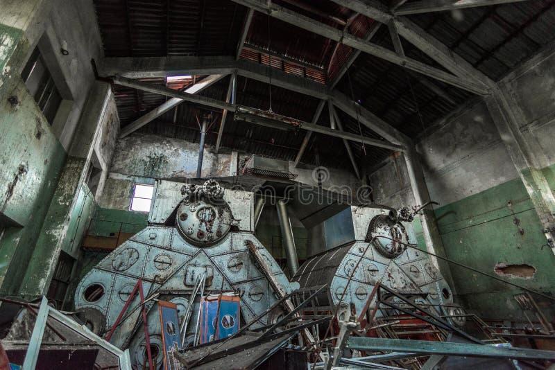 有巨型古色古香的锅炉的被放弃的工厂飞机棚 库存图片
