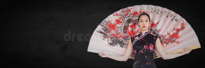 有巨型爱好者的艺妓反对黑暗的木盘区 免版税库存图片