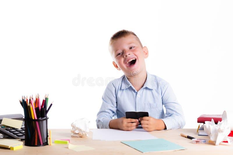 有巨大的微笑的逗人喜爱的矮小的男生在他的书桌坐wh 免版税库存图片