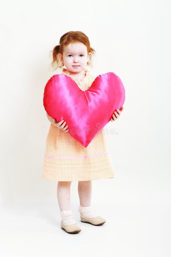 有巨大的明亮的红色心脏的小女孩 免版税库存图片