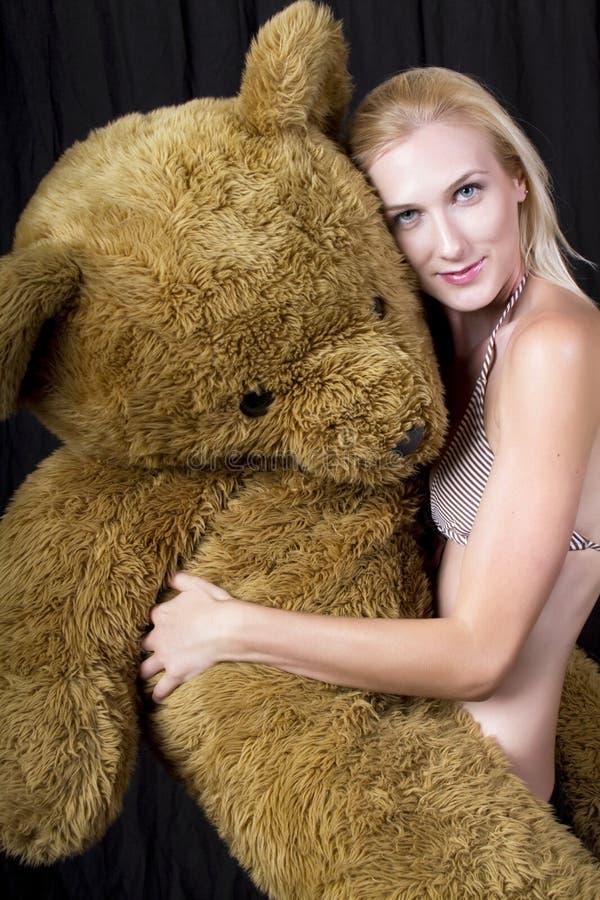 有巨大的玩具熊的一个美丽的年轻金发碧眼的女人 库存照片