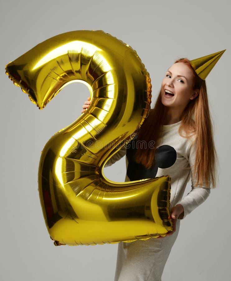 有巨大的金数字气球的年轻愉快的女孩作为生日聚会的一个礼物 免版税库存图片