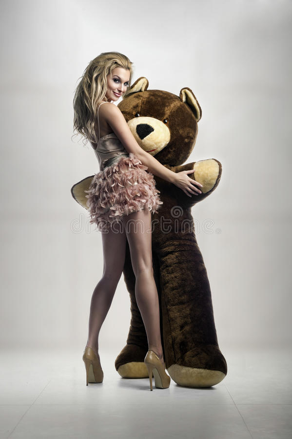 有巨大teddybear的性感的金发碧眼的女人 免版税库存照片