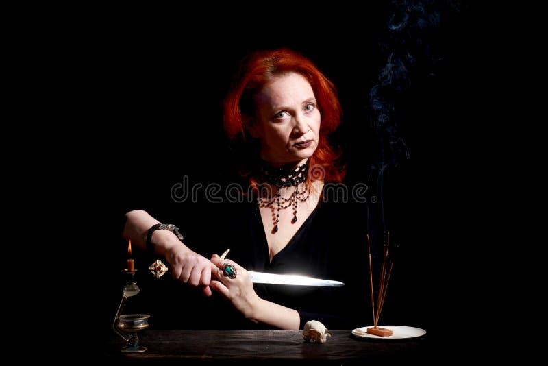 有巫术师短剑的巫婆 有不可思议的装饰和活表示的好情感红头发人巫婆 图库摄影