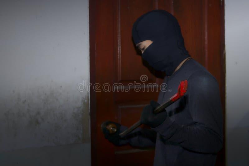 有巴拉克拉法帽的被掩没的窃贼使用对闯入的撬杠房子在夜间 砖概念罪行前面现有量苛刻的藏品手枪影子墙壁 免版税库存照片