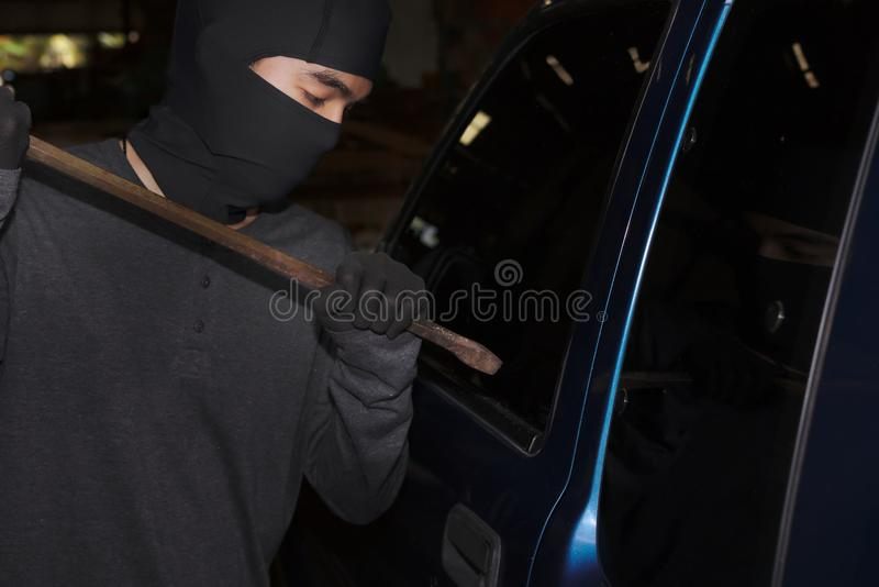 有巴拉克拉法帽的被掩没的窃贼使用对闯进的撬杠汽车 砖概念罪行前面现有量苛刻的藏品手枪影子墙壁 免版税图库摄影