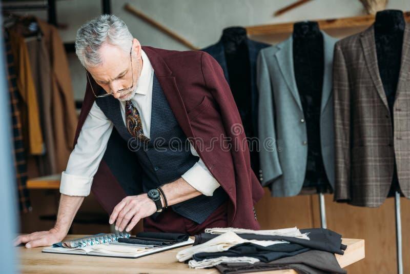有布料类型和夹克编目的时髦的成熟裁缝在肩膀在工作场所 库存照片