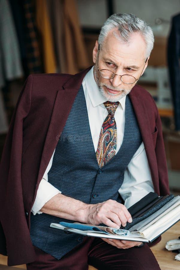 有布料类型编目的时髦的成熟裁缝坐桌 库存照片