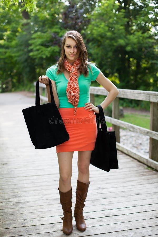 有布料购物袋的美丽的女孩走在木桥的 图库摄影