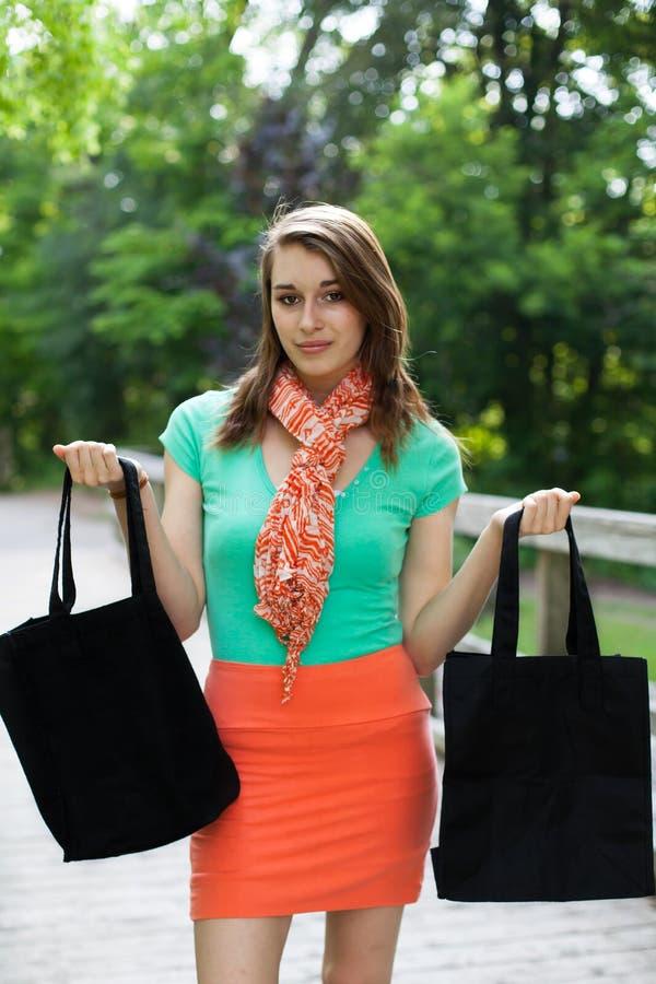 有布料购物袋的美丽的女孩走在木桥的 库存照片