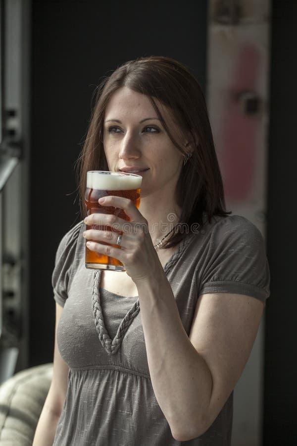 有布朗头发的美丽的少妇喝一品脱的 免版税库存图片