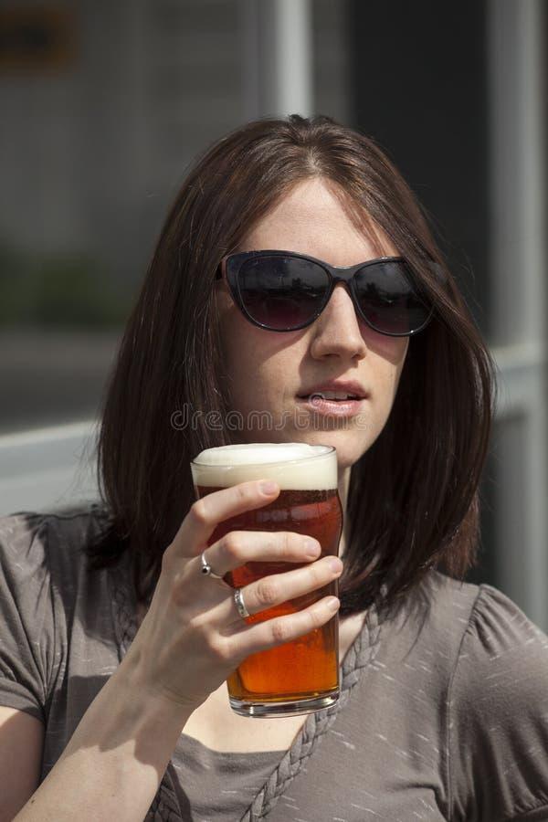 有布朗头发的美丽的少妇喝一品脱的 库存照片