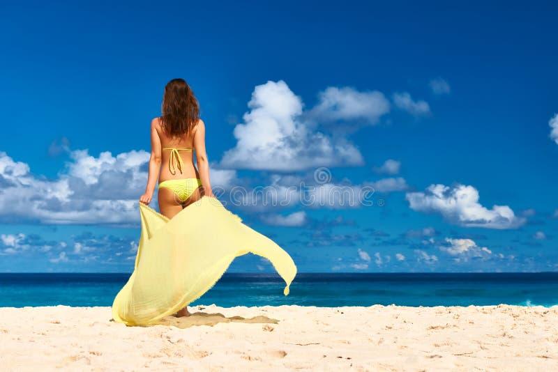 有布裙的妇女在海滩 库存图片