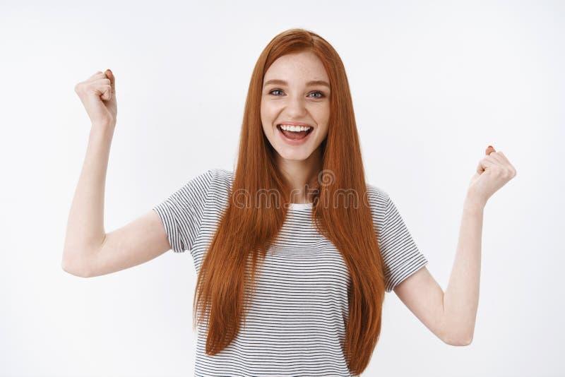 有希望的迷人的可爱的可爱的欢呼红头发人少女的蓝眼睛提高欢欣的拳头高幸福 图库摄影