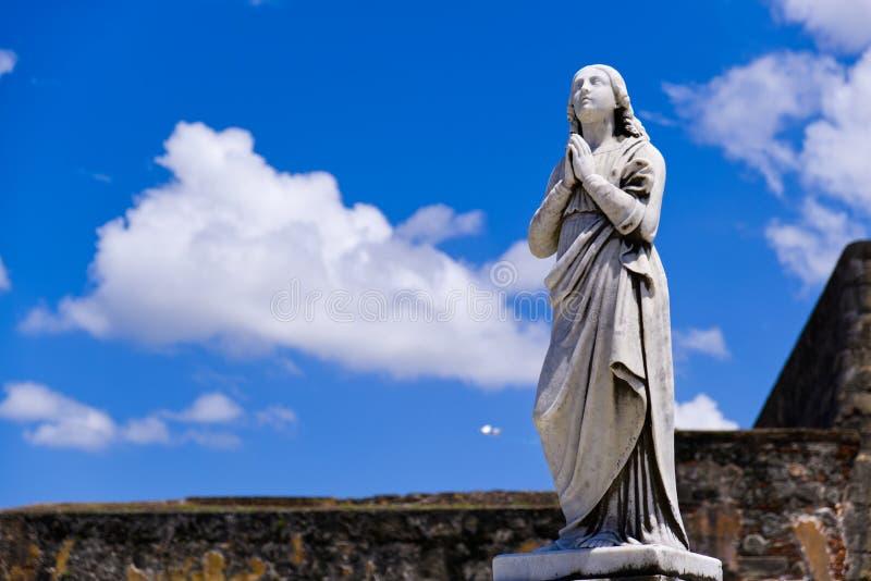 有希望的雕象年轻女人祈祷 库存照片