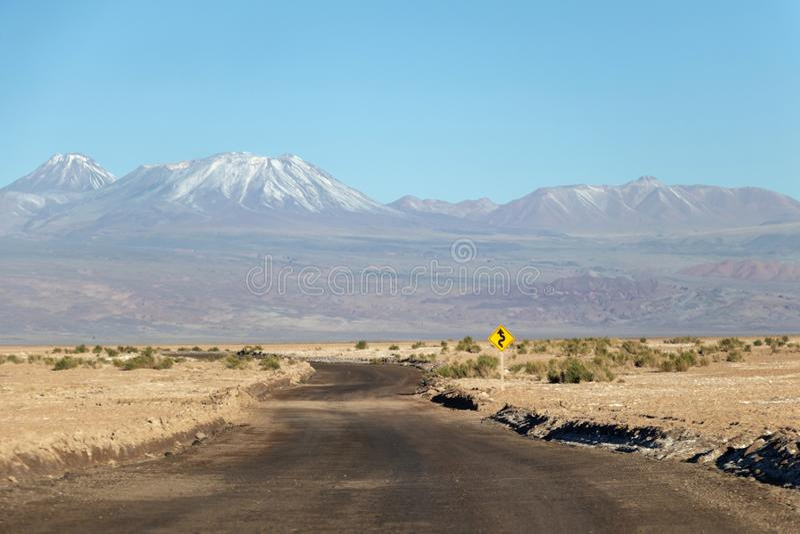 有带领往雪的黄色路标的长的直路在阿塔卡马沙漠,智利加盖了山 免版税库存照片
