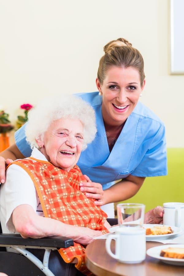 有帮助与膳食的资深妇女的护士 免版税库存图片