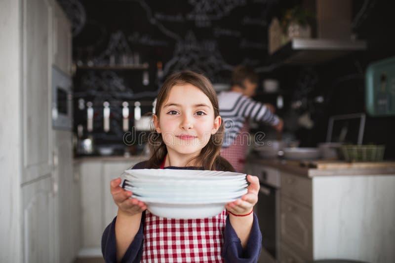 有帮助在厨房里的祖母的一个小女孩 免版税库存图片