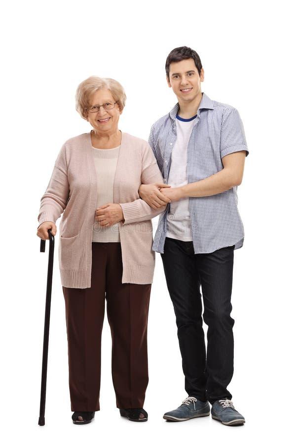 有帮助她的走的藤茎和年轻人的年长夫人 库存图片