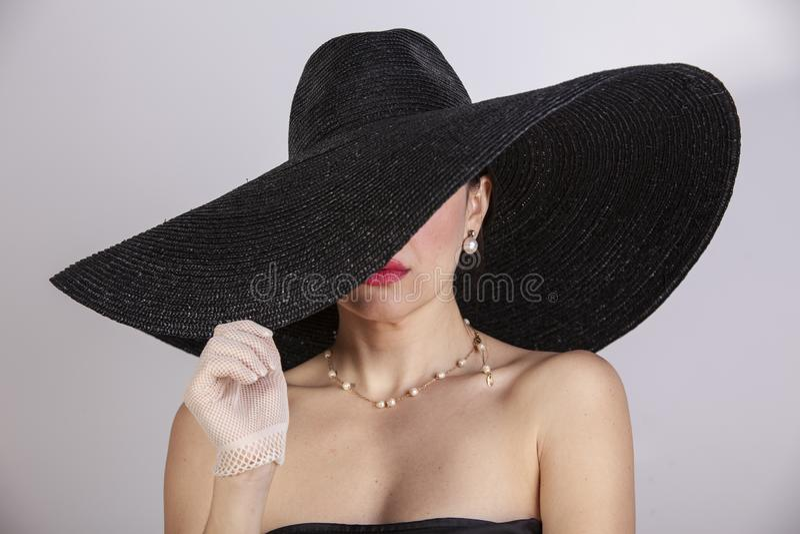 有帽子、手套、首饰和红色嘴唇的美女 减速火箭的方式 免版税图库摄影