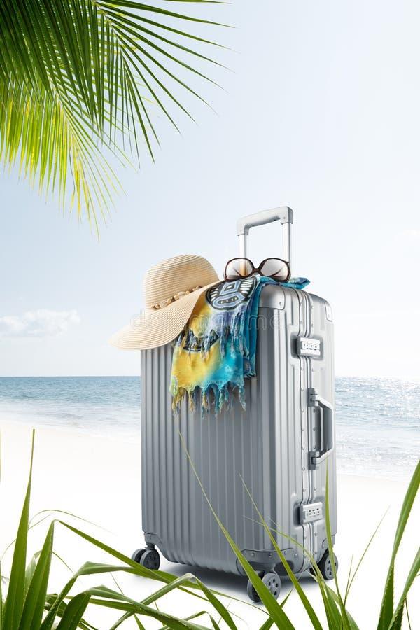 有帽子、pareo和太阳镜的手提箱在晴朗的热带海滩 图库摄影