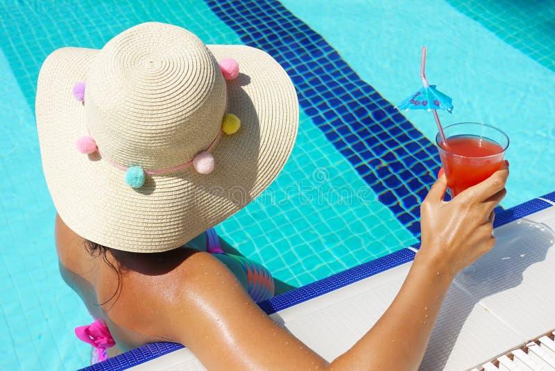 有帽子和五颜六色的泳装饮用的鸡尾酒的少妇在游泳池 库存图片