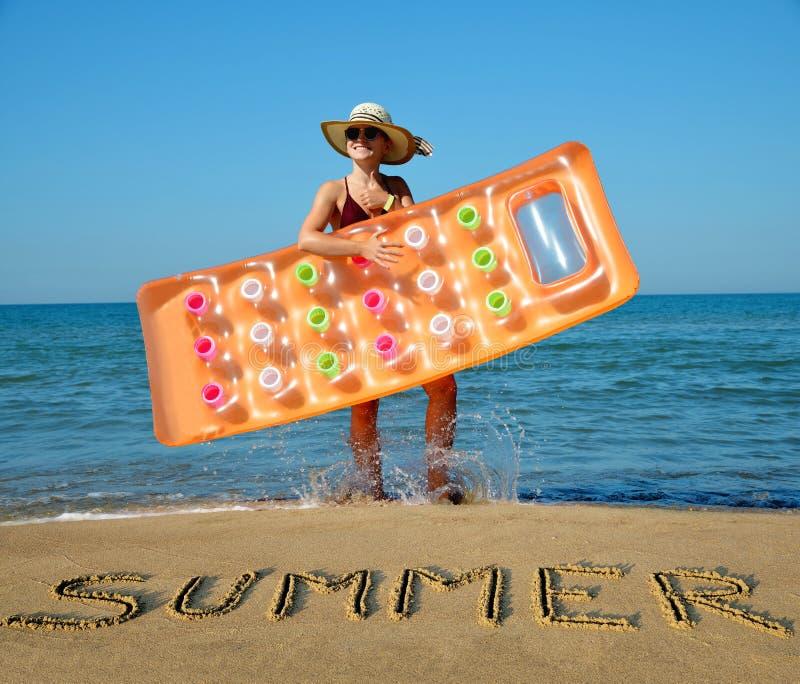 有帽子和可膨胀的床垫的白种人女孩在海滩 图库摄影