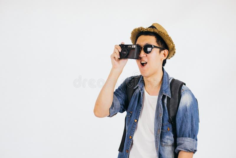 有帽子和太阳镜的年轻亚裔游人微笑和拿着照相机的被隔绝在白色背景 免版税库存照片