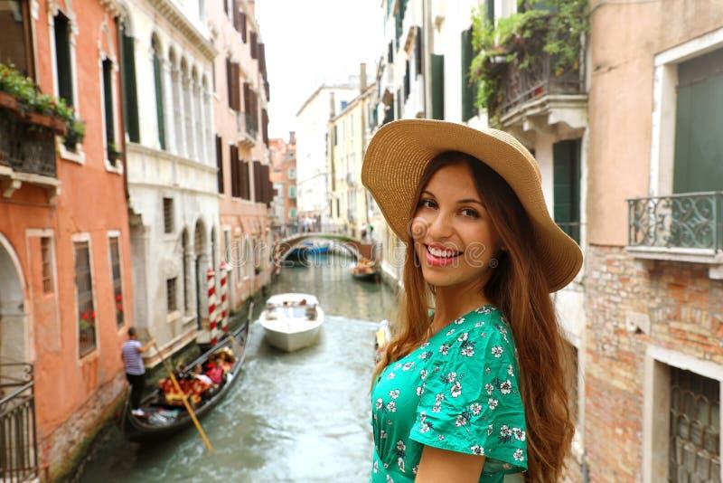有帽子和绿色礼服的微笑的快乐的妇女在她的威尼斯式假日 在照相机的愉快的有吸引力的女孩微笑在威尼斯,意大利 免版税库存照片