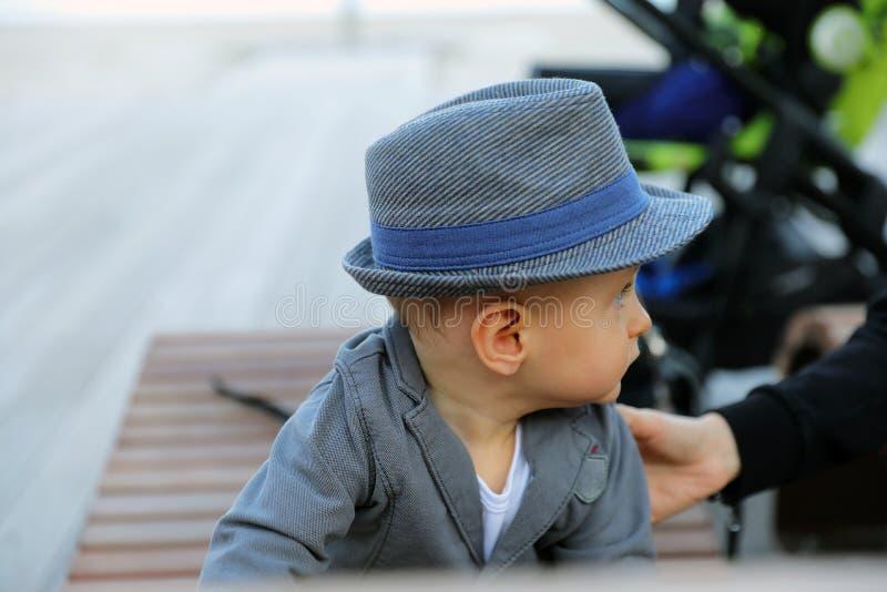 有帽子和衣服夹克的美丽的男婴 免版税库存图片