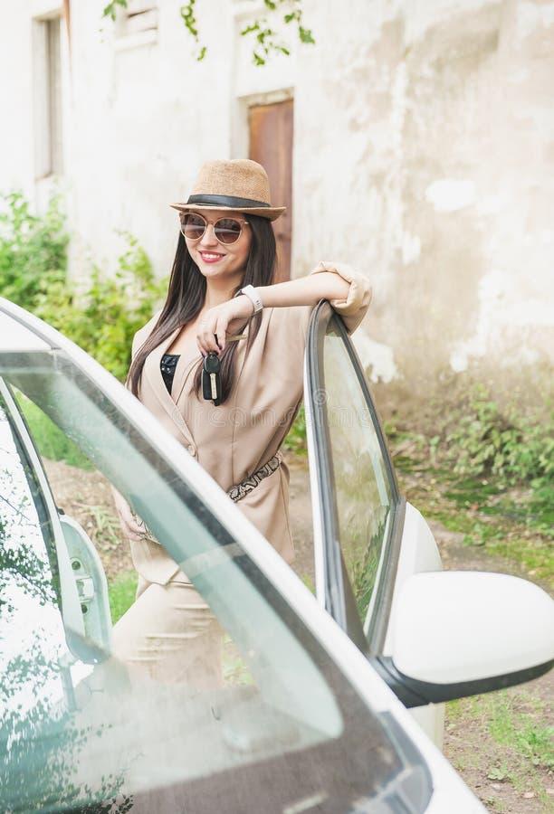 有帽子和镜片的美丽的年轻女人在汽车 免版税库存照片