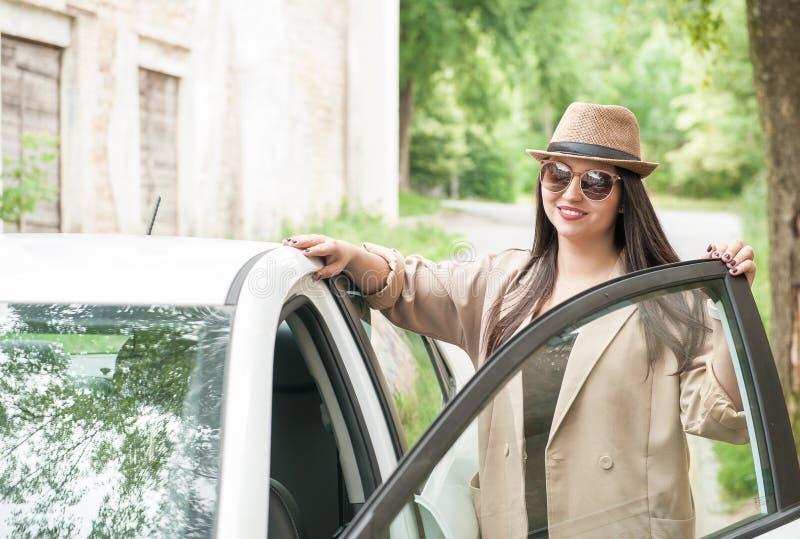 有帽子和镜片的美丽的年轻女人在汽车 库存照片